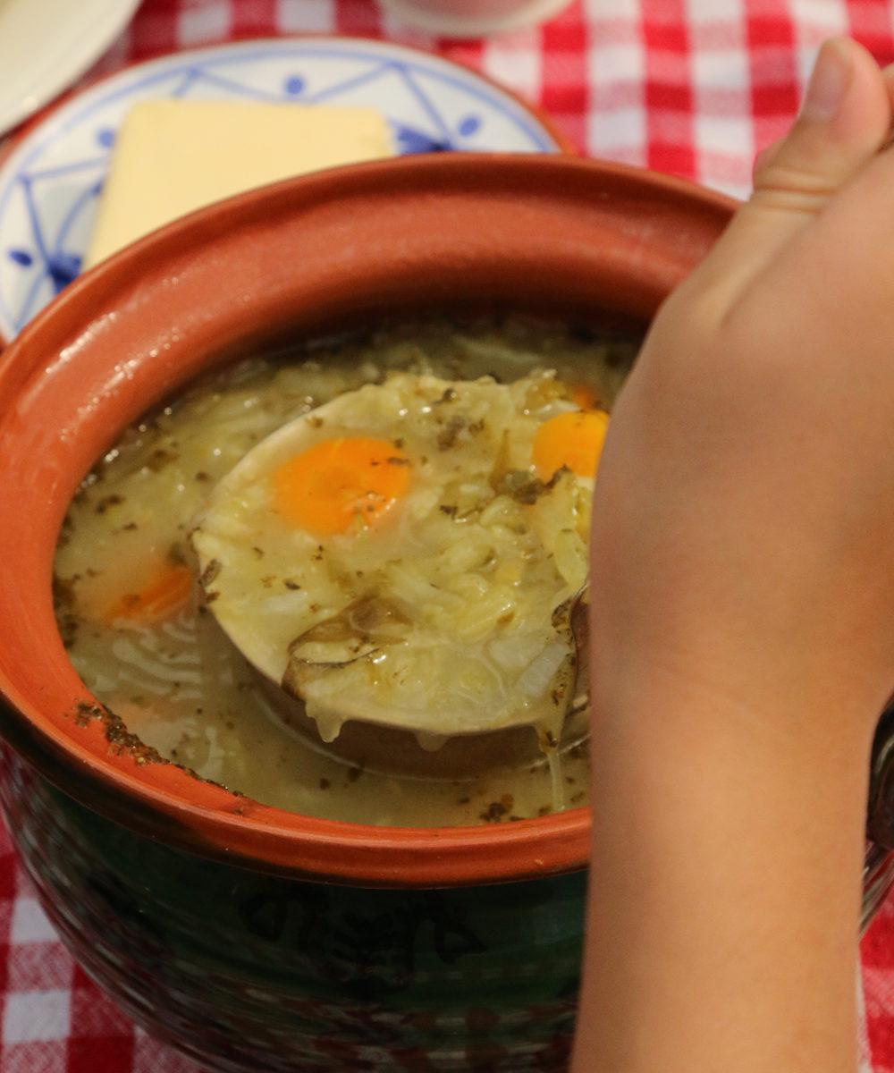 Zdjęcie przedstawia kogoś nalewającego zupę do miski
