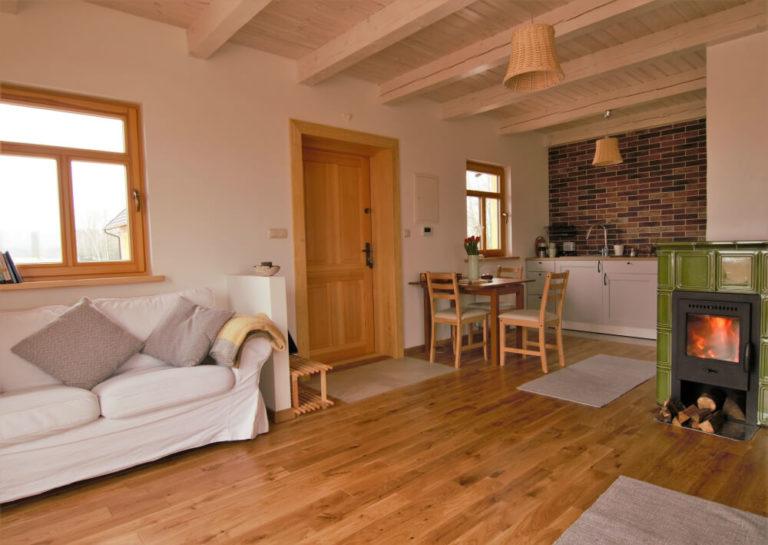Zdjęcie przedstawia kuchnie w domu w Czarnej Hańczy. Widać na nim kominek i sofę w części salonowej, a w części kuchennej aneks kuchenny i stół